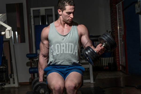 young bodybuilder doing heavy weight exercise for biceps with dumbbell