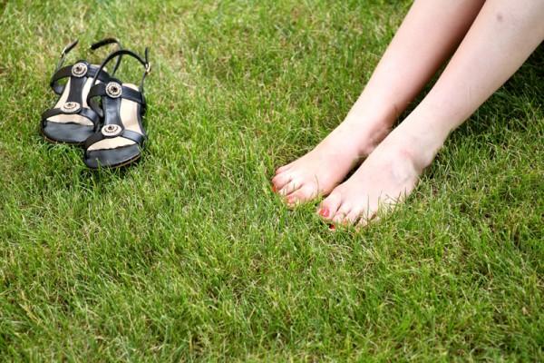 Womans bare feet on green grass