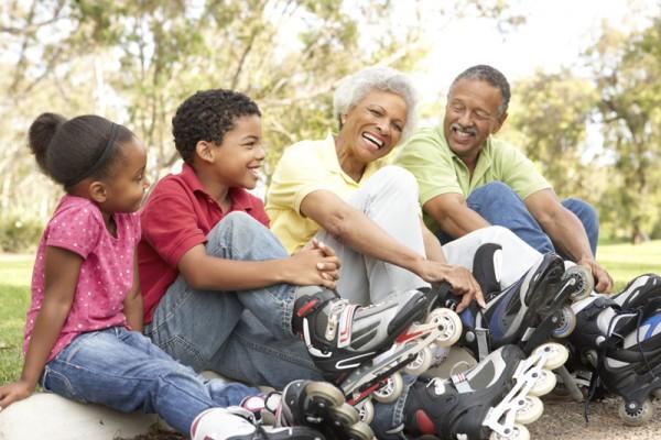 Grandparent With Grandchildren Putting On In Line Skates In Park