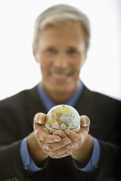 Businessman holding world.