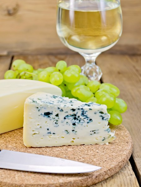 Cheese different with grapes and wine on the board