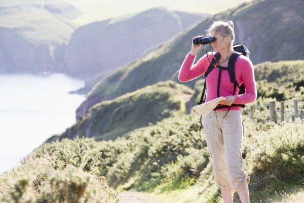 Woman on cliffside path using binoculars