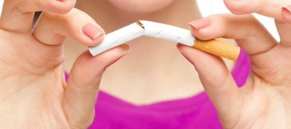 Young woman is breaking a cigarette, quit smoking concept, isolated over white