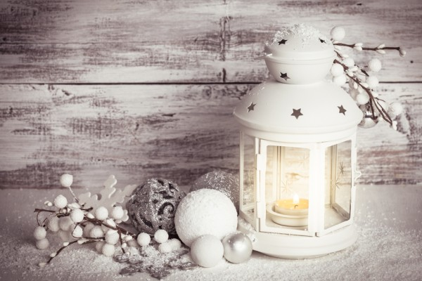 Cristmas lantern with decorations and snow over white shabby wooden background