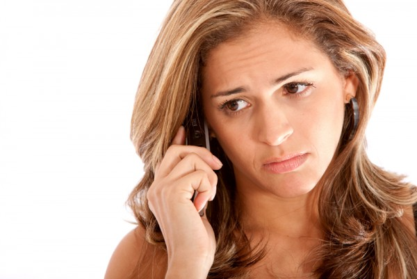 Business woman looking sad on the phone isolated over a white background