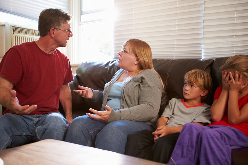 Family Sitting On Sofa With Parents Arguing