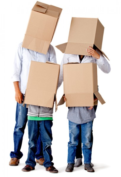 Family with cardboard boxes on their heads in a fun moving day – isolated