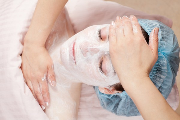 Beautiful woman with clear skin getting beauty treatment of her face at salon. Clear Skin.