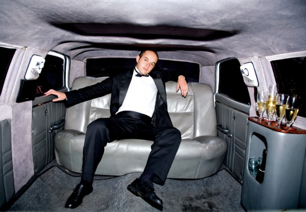 guy inside a limousine all alone with some champagne