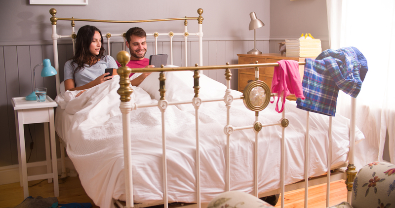 Young Couple In Bed Using Digital Tablet And Mobile Phone
