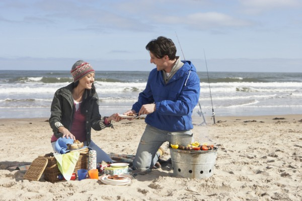 Couple Having Barbeque On Winter Beach