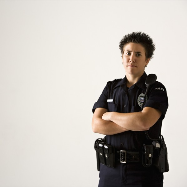 Portrait of mid adult Caucasian policewoman standing with hand on gun holster looking at viewer.