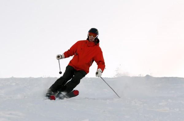 Man skiing in the orange jacket on the mountain