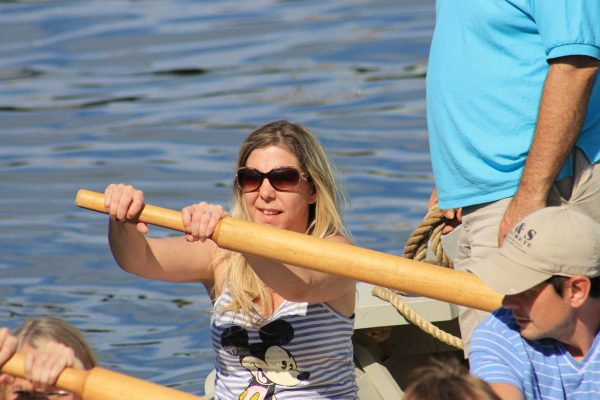 Rachel lends her strength to row a boat full of vacationers.